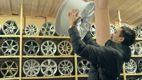 The man buys alloy wheels in his shop for his car. He takes a disc out of the box and looks at it. The white wheel is very beautiful and steep. Drawing and Stock Image