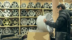 The man buys alloy wheels in his shop for his car. He takes a disc out of the box and looks at it. The white wheel is very beautiful and steep. Drawing and stock video footage