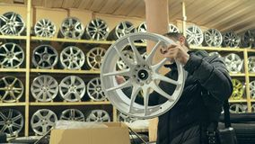 The man buys alloy wheels in his shop for his car. He takes a disc out of the box and looks at it. The white wheel is very beautiful and steep. Drawing and Royalty Free Stock Photos