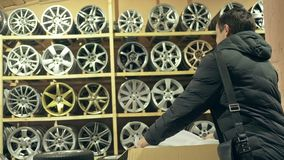 The man buys alloy wheels in his shop for his car. A man packs a disc in a box. The white wheel is very beautiful and steep. Drawing and form of the disc are stock video footage