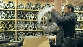 The man buys alloy wheels in his shop for his car. He takes a disc out of the box and looks at it. The white wheel is very beautiful and steep. Drawing and Stock Images