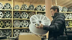 The man buys alloy wheels in his shop for his car. He takes a disc out of the box and looks at it. The white wheel is very beautiful and steep. Drawing and Stock Photo