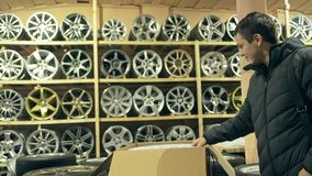 The man buys alloy wheels in his shop for his car. He takes a disc out of the box and looks at it. The white wheel is very beautiful and steep. Drawing and Royalty Free Stock Image