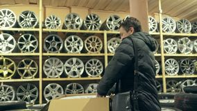 The man buys alloy wheels in his shop for his car. He takes a disc out of the box and looks at it. The white wheel is very beautiful and steep. Drawing and stock video