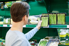 Man buys asparagus in store Royalty Free Stock Photography