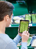 Man buys a asparagus in store Stock Photography