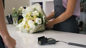 Man buys bouquet in flower shop pays by card in payment terminal, hands closeup.