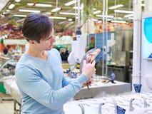 Man buys carp in fish shop Royalty Free Stock Photos