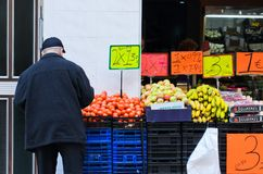 A man buys fruit in a grocery store. BARCELONA, SPAIN - APRIL 11, 2014: A man buys fruit in a grocery store in the neighborhood of Clot in Barcelona stock photo