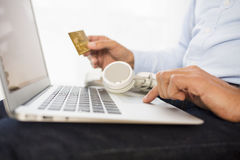 Man buys music on-line on computer with credit card, e-commerce Stock Images