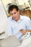 A man buys music online on computer, at home Royalty Free Stock Photos