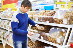 Man buys nuts in a supermarket Royalty Free Stock Photo