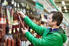Man buys uncooked smoked sausage in supermarket Royalty Free Stock Photos