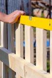 Man byggande av ett trästaket och att kontrollera med andenivån clos Arkivfoton