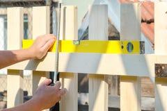 Man byggande av ett trästaket och att kontrollera med andenivån Stäng sig upp av hans hand och hjälpmedlet i ett DIY-begrepp Royaltyfria Bilder