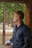 Man at a cabin. A handsome man looking out the window of a mountain cabin Royalty Free Stock Image