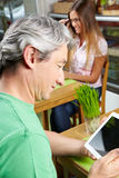 Man in café looking at tablet Royalty Free Stock Images