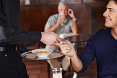 Man in café paying with credit card Royalty Free Stock Photos