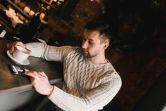 Man in cafe with cup of coffe. Lifestyle portrait of handsome boy in sweater. Rustic styling.  Stock Images