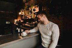 Man in cafe with cup of coffe. Lifestyle portrait of handsome boy in sweater. Rustic styling.  Stock Photos