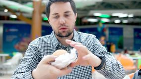 Man in cafe of fast food unpacks burger. Unhealthy food. stock video footage