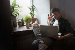 A man in a cafe with a laptop does work in a cozy place with a cup of coffee, gets pleasure. The concept of freelancing royalty free stock image