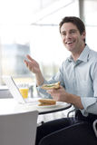 A man in a cafe or office canteen, working on a laptop Stock Photo