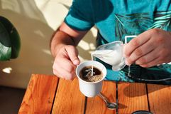 A man in a cafe pours cream into a Cup of coffee in the morning. Breakfast. stock images