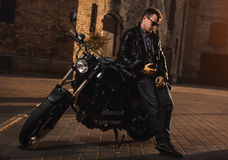 Man with a cafe-racer motorcycle. Outdoors stock image