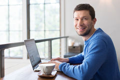 Man in cafe. Smiling man working on laptop computer in cafe drinking coffee, lifestyle concept Royalty Free Stock Image