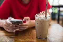 Play smartphone near ice mocha coffee. Man in cafe using smartphone to chat and play social media near Ice mocha coffee with whip cream in cafe. Relax lifestyle Stock Photo