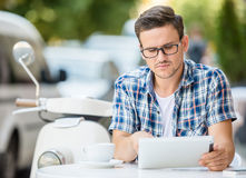 Man in cafe. Young man is using digital tablet while sitting in the sidewalk cafe Stock Photo
