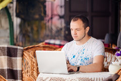 Man in caffee works on his laptop Stock Photography