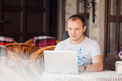Man in caffee works on his laptop Royalty Free Stock Images