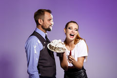 Man with cake on face and brutal girl holding chilli over purple background. Royalty Free Stock Photos