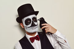 Man with calaveras makeup and a black crow Royalty Free Stock Images
