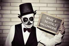Man with calaveras makeup, with chalkboard with text have a deat Stock Images