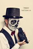 Man with calaveras makeup and crow, and text happy halloween Royalty Free Stock Image