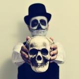 Man with calaveras makeup holding a skull Stock Photography