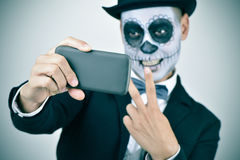 Man with calaveras makeup taking a selfie Stock Photo