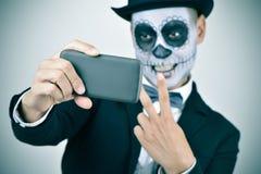 Man with calaveras makeup taking a selfie Stock Photo