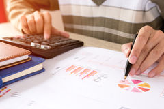 Man calculate about cost and charts report on table at home office, calculator on desk of financial planing. Finance concepts. Man calculate about cost and Stock Image