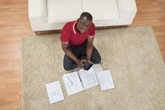 Man Calculating Invoices Using Calculator Stock Image