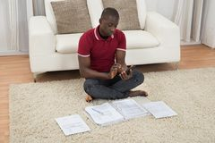 Man Calculating Invoices Using Calculator Royalty Free Stock Photography