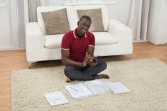 Man Calculating Invoices Using Calculator Royalty Free Stock Image