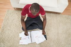 Man Calculating Invoices Using Calculator Royalty Free Stock Photo