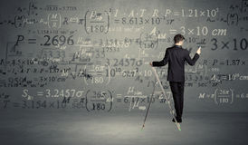 Man calculating from ladder Royalty Free Stock Image