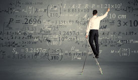 Man calculating from ladder Stock Photos
