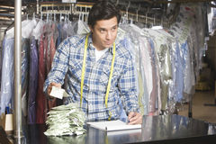 Man Calculating Receipts While Writing On Notepad In Laundry Royalty Free Stock Image