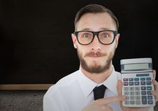 Man with calculator against blackboard Stock Images